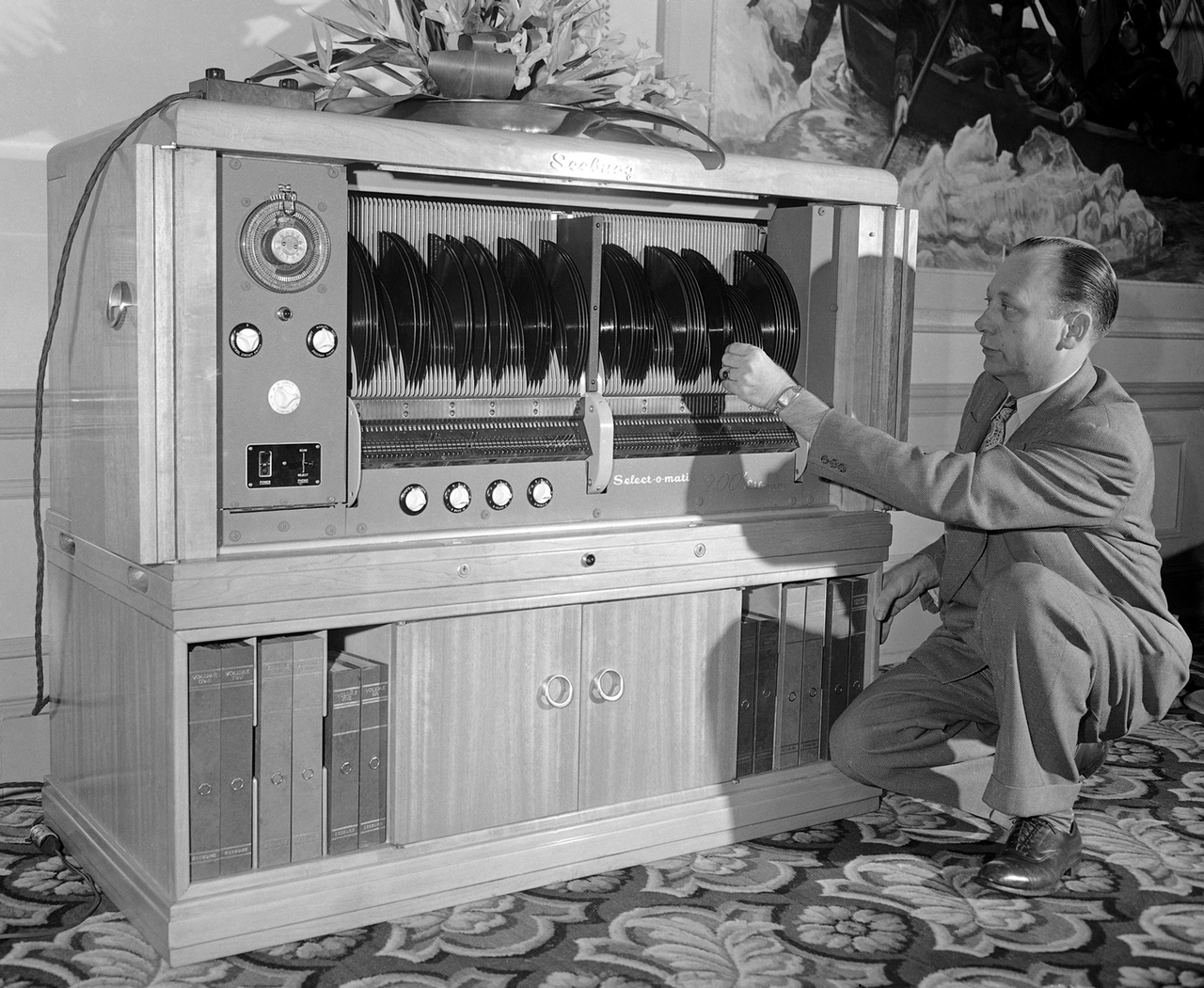 "Myron Holbert, shown with the Seeburg Selec-O-Matic ""200"" library demonstrated for the first time in Los Angeles, April 2, 1948. It stores and automatically plays 200 selections which are accomplished by merely setting a lever to play either side or both sides of any record in the whole library and the whole library can be played without anyone touching the records. A revolutionary development is the playing of both sides of the record without turning it over. (AP Photo)"