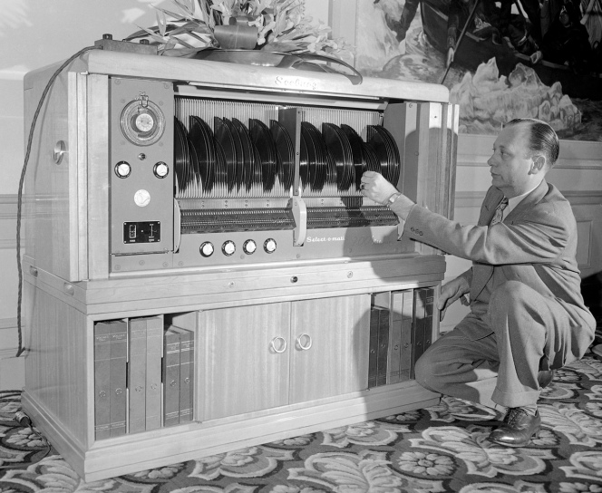 """Myron Holbert, shown with the Seeburg Selec-O-Matic """"200"""" library demonstrated for the first time in Los Angeles, April 2, 1948. It stores and automatically plays 200 selections which are accomplished by merely setting a lever to play either side or both sides of any record in the whole library and the whole library can be played without anyone touching the records. A revolutionary development is the playing of both sides of the record without turning it over. (AP Photo)"""