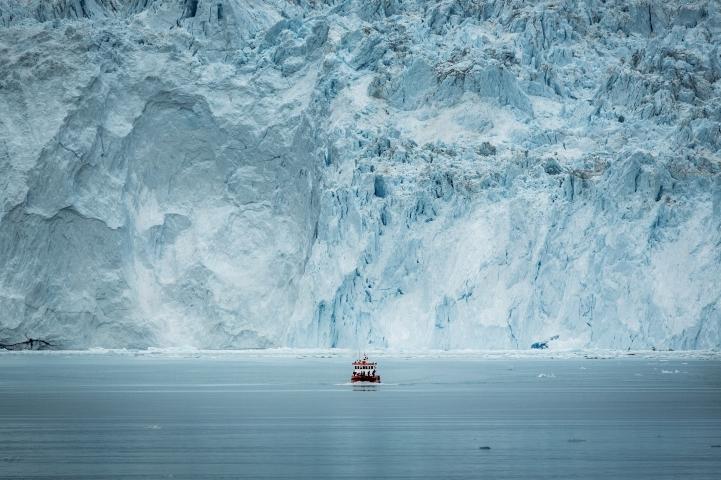 AsmallpassengerboatinfrontofthehugeglacierwallattheEqiglacierinGreenlandMadsPihl